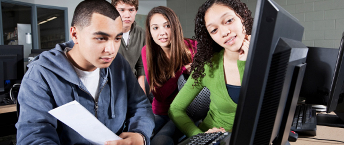 an image of four students crowded around a computer working together