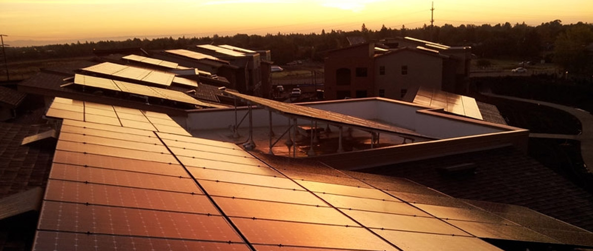 an image of some rooftop solar panels glistening in the sunset
